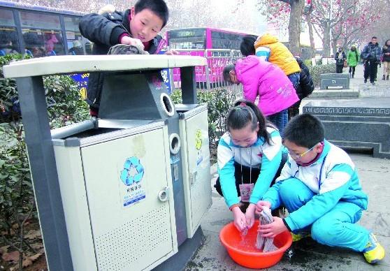 小学生们擦洗垃圾箱